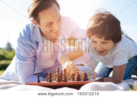 Intelligence is the key. Enthusiastic motivated clever guy encouraging his child playing chess and admiring his quick mind and strategy