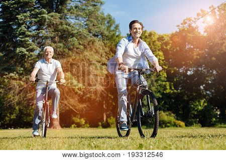 Unconventional bond. Attentive supportive wonderful man inviting his dad riding bikes with him while enjoying warm weather in the park