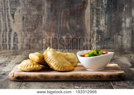 Typical Spanish empanadas on wooden table background