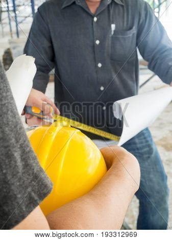 Engineer Discussing With Foreman About Project In Building Construction Site, Selective Focus