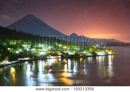 Colorful Amed harbor in the night and the highest point of the island Agung volcano (3142 m) is visible on the background.