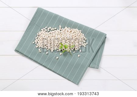 pile of raw white beans on grey place mat