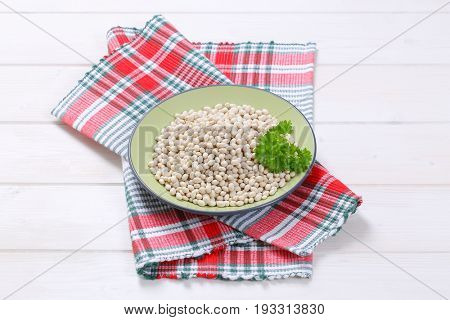 plate of raw white beans on checkered dishtowel