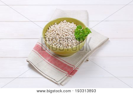 bowl of raw white beans on folded place mat