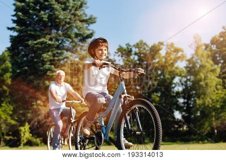 Healthy and fun. Bright sweet optimistic child enjoying his hobby while spending the day outdoors and riding bicycles with his grandpa