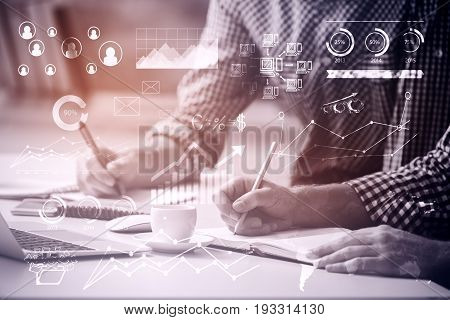 Businessmen doing paperwork at workplace with business graphs and coffee cup. Partnership concept. Toned image. Double exposure
