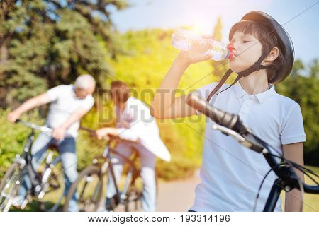 Nurturing moisture. Emotional engaged cool kid spending the day with his family and riding bikes with them while stopping for a gulp of water