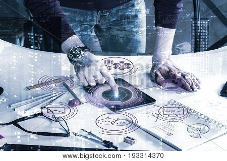 Businessman using tablet with abstract menu hologram and leaning on office desktop with supplies and other items on night city background. Communication concept. Double exposure