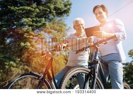 Connection everywhere. Emotional lively handsome gentleman talking his father exciting news while receiving an email while they riding bicycles together