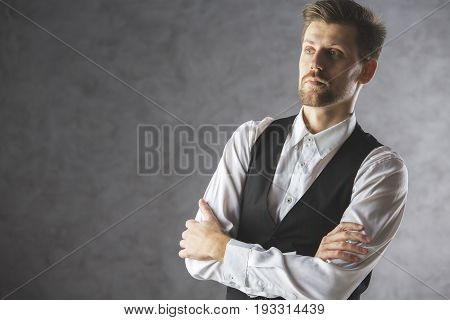 Portrait of handsome young businessman with folded arms on concrete background with copy space