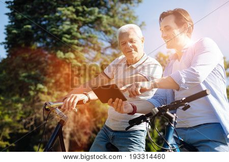 Electronic guide. Energetic savvy optimistic gentleman using his gadget for showing his father a map and deciding on their destination