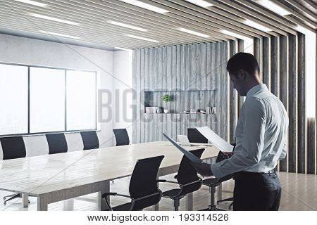 Side view of businessman with documents standing in modern conference room interior with equipment and bright daylight. Executive concept. 3D Rendering