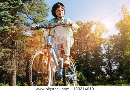 Going further than ever. Bright emotional clever kid exploring new places while reading his bicycle and wearing special helmet