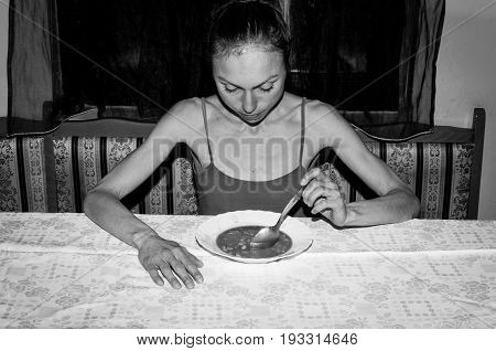 Anorexia. Skinny anorexic girl holding a spoon and look at the plate with food. Black and white.