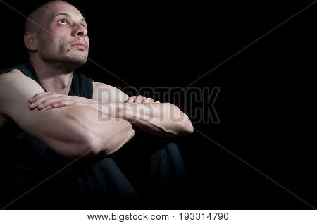 Seeking for God. Young man looking above. Dark image. Black background. Loneliness. Sadness. Depression.