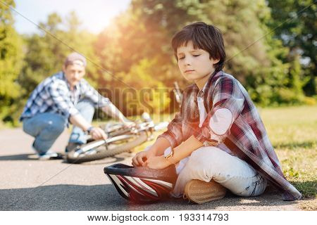 Dont be sad. Expressive joyless sweet child sitting on the road and waiting while his dad repairing the bicycle