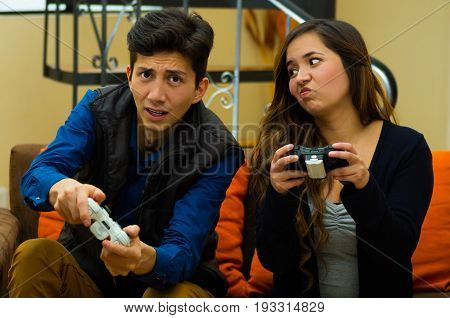 Handsome young man playing video games, woman with a bored expresion in her face, on the couch, concept about home entertainment, video games.