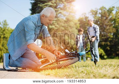Skilled technician. Passionate skillful elderly gentleman dedicating a moment for fixing some issues before taking a ride around the park with his family