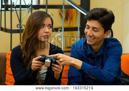 Handsome young man teaching how to play the video games to his bored girlfriend, on the couch, concept about home entertainment, video games.