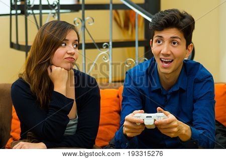 Handsome young man playing video games on the couch while girlfriend is bored, concept about home entertainment, video games.