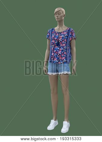 Full-length female mannequin dressed in colorful blouse and blue shorts. Isolated on green background. No brand names or copyright objects.