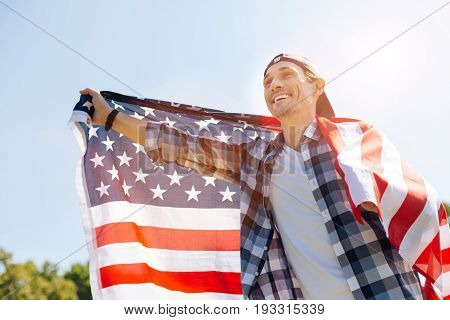 Patriotic feelings. Handsome emotional sincere gentleman enjoying a picnic and holding up a flag while feeling patriotic during the festive day