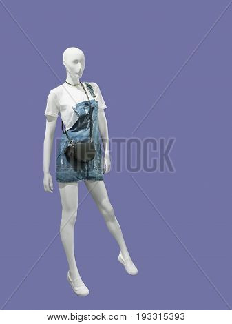Female mannequin dressed in overalls and t-shirt isolated. No brand names or copyright objects.