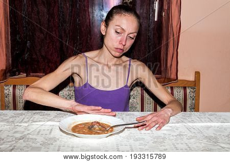 Anorexia. Young skinny woman with anorexia refusing to eat.