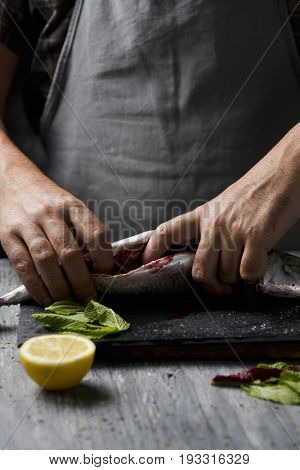 closeup of a young caucasian man with a gray apron emptying the entrails of a raw fresh mackerel, on a slate tray placed on a rustic wooden table or countertop