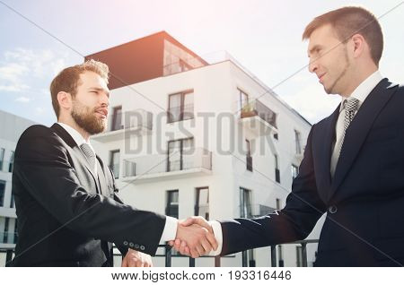 Two men are standing on the balcony and shaking hands. Investor or customer buying apartment