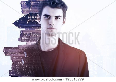 Portrait of pensive young businessman on sideways city background. Tomorrow concept. Double exposure