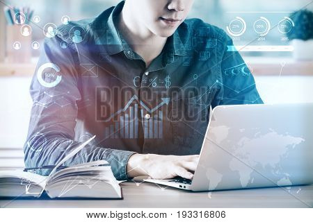 Young businessman at workplace using laptop computer placed on desk with open book and abstract business diagrams. Accountant concept. Double exposure