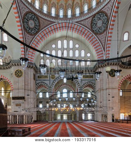 Istanbul, Turkey - April 19, 2017: Interior of Suleymaniye Mosque, an Ottoman Baroque style mosque completed in 1755, with huge arches & many colored stained glass windows, Fatih district