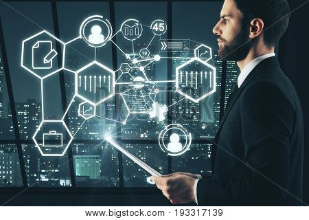 Side view of handsome young businessman with document in hand and abstract digital business icons standing in interior with night city view. Touchscreen concept. 3D Rendering