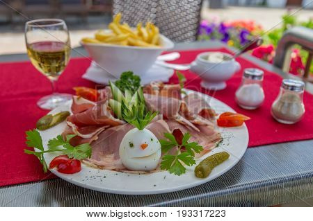 Stylish ham french fries and salad dish with funny decorated egg white wine glass mayonnaise salt and pepper on the background