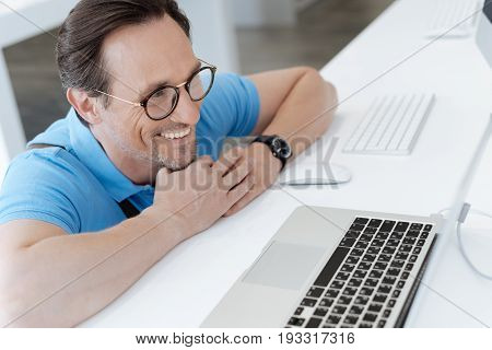 What a perfect gift. Smiling male shopper wearing glasses grinning widely while admiring the latest laptop model staying on a display while shopping at an electronics store.