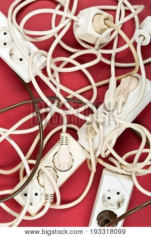 Cable chaos clutter from multiple electric wire extension cords and multi-contact plugs on red background