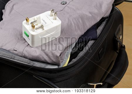 Travel power adapter with connectors for european UK and US power plugs on packed suitcase with clothings - travel preparation
