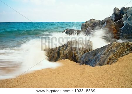 Salty sea water, waves, sun, sand, rocks and holidays. Summer and heat. Sea waves hitting the rocky beach at Malgrat de Mar, Spain.