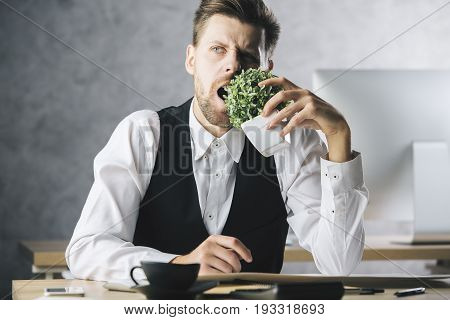 Crazy businessman eating plant at workplace with coffee cup supplies and other items