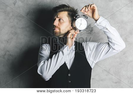 Businessman listening to silver alarm clock mechanism on concrete background with shadow