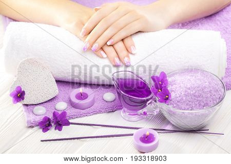 Beautiful Purple Manicure With Violet, Candle And Towel On The White Wooden Table.