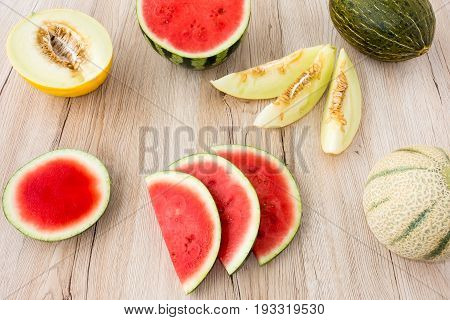 Arrangement of a variety of whole halved and sliced melons on light brown wooden background.