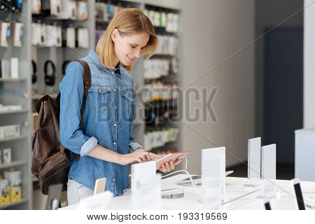 Need to pick up new one. Side view on a female customer standing at a display and using a mockup tablet computer while visiting an electronics store.