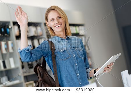 Hey there. Waist up shot of a positive female customer grinning widely while holding template laptop at a display and waving into the camera.