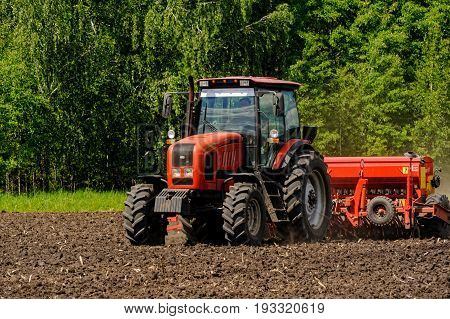 Farmer Seeding Crops On Tractor At Field. Russia