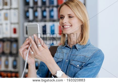 Portrait of a female customer wearing a jean shirt standing at a store display and trying out the latest model of a smartphone while shopping at an electronics store.