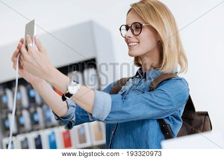 Side view on a cheerful shopper wearing glasses taking self portrait with template phone while standing at a display and shopping for a new gadget at store.