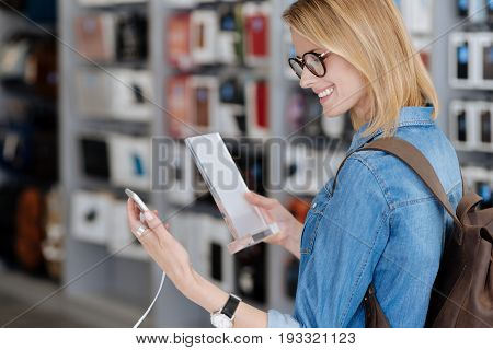 Shot of a smiling woman with a backpack looking at a smartphone while holding a product information plate and shopping for new technological devices.