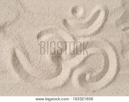 Om symbol written in sand view from above have a break or meditation concept